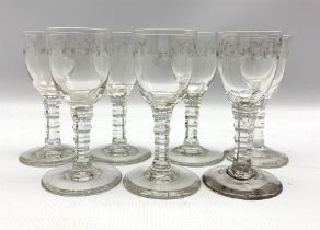 Seven 19th century cordial glasses decorated with trailing garlands on facet cut stems H13cm
