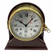Eight-day 20th century brass cased ships bulkhead clock mounted on a mahogany effect display stand