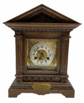 An early twentieth century German oak mantle clock in an architectural case on a shaped plinth with