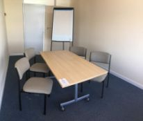 A light wood veneer table, four chairs and a flip chart