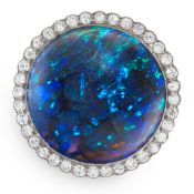 A BLACK OPAL AND DIAMOND RING in platinum, set with a central round cut black opal of 23.38