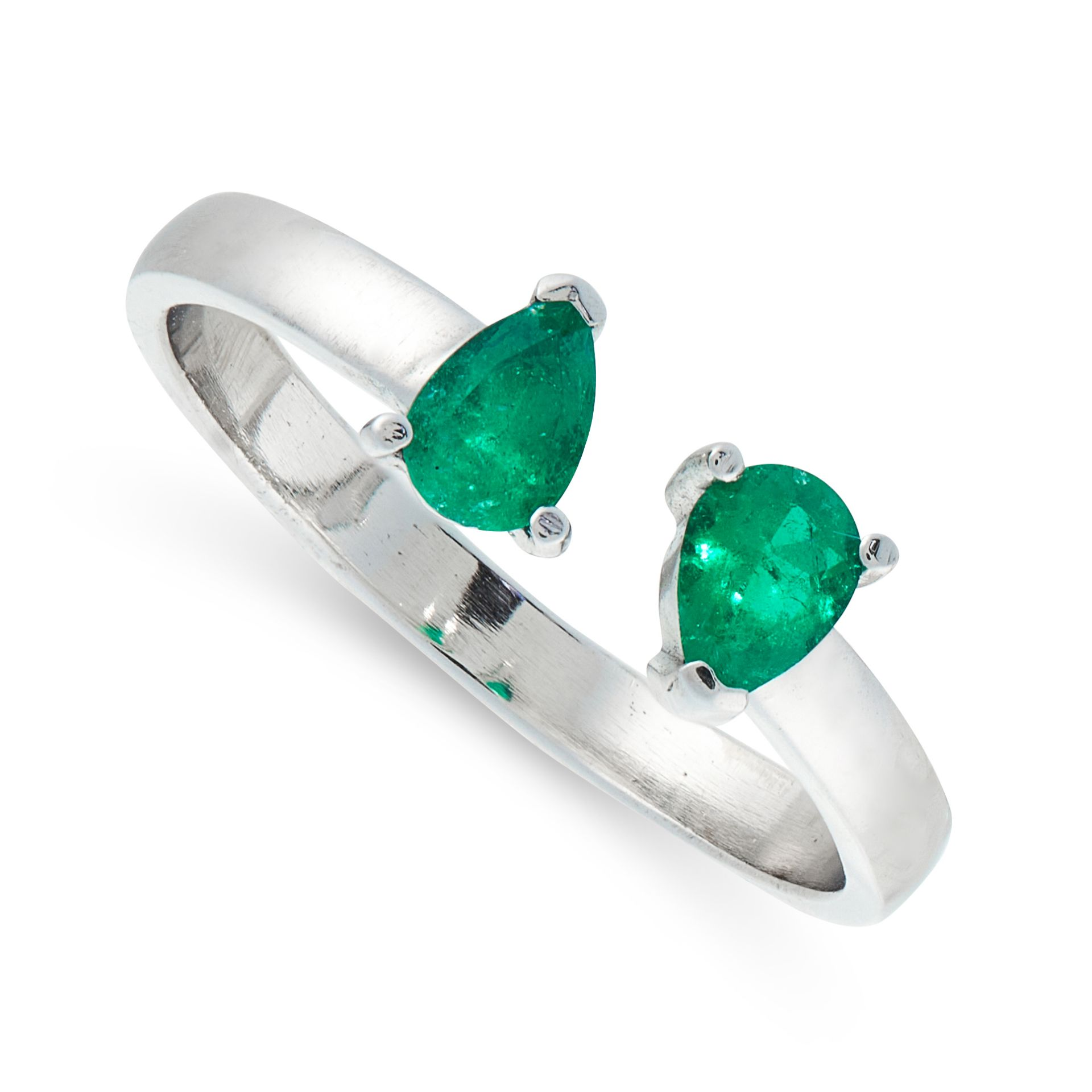 AN EMERALD DRESS RING in 18ct white gold, the open band is set with two pear cut emeralds, stamped