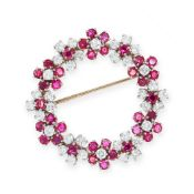 A RUBY AND DIAMOND BROOCH designed as a circular wreath of flowers set with clusters of round cut