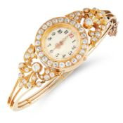 A DIAMOND WATCH BANGLE, EARLY 20TH CENTURY in high carat yellow gold, the circular face within a
