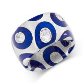 A DIAMOND AND ENAMEL RING in 18ct white gold, the band with blue enamel design, set with a trio of