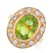 PERIDOT AND DIAMOND RING of cluster design, collet-set with an oval peridot within a border of
