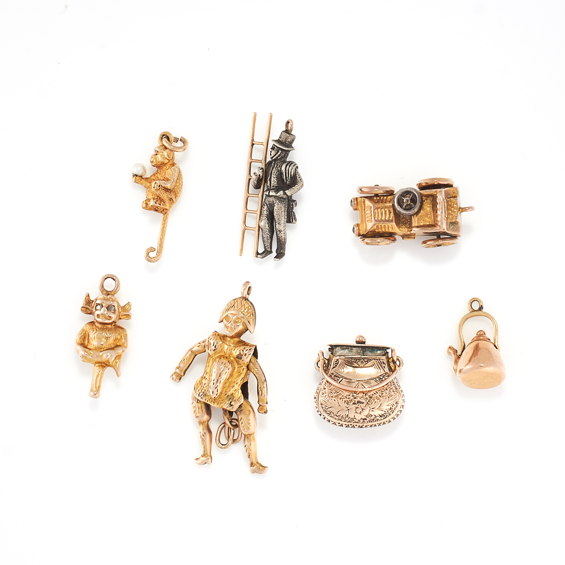 A MIXED LOT OF CHARMS some in yellow gold, comprising of two monkey charms, a tea pot charm, a purse