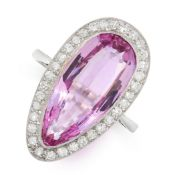 A PINK TOPAZ AND DIAMOND RING in platinum, set with a pear cut pink topaz of 7.11 carats, within a