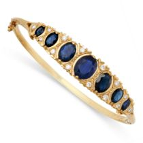 A SAPPHIRE AND DIAMOND BANGLE in 9ct yellow gold, the hinged body set to one half with a row of
