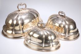 ^ A GRADUATED SET OF THREE SILVER-PLATED MEAT COVERS