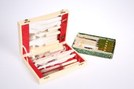 A boxed set of six green handled knives, together with a boxed set of six fish knives and forks.