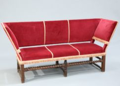 A 19TH CENTURY OAK AND UPHOLSTERED SETTEE