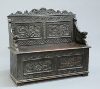 A VICTORIAN CARVED OAK BOX SETTLE