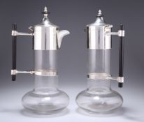 A NEAR PAIR OF SILVER-PLATE MOUNTED CLARET JUGS