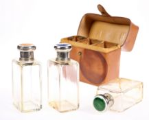 A SET OF THREE CASED CUT GLASS BOTTLES