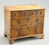 A SMALL FEATHER BANDED AND CROSSBANDED WALNUT CHEST OF DRAWERS