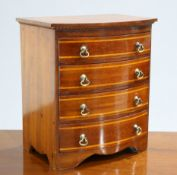 A BOW-FRONT MINIATURE CHEST OF DRAWERS