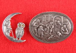 A OWL AND MOON BROOCH AND A BROOCH EMBOSSED WITH A TAVERN SCENE