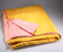 A VINTAGE MUSTARD AND PINK COTTON QUILT