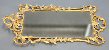 A LARGE ROCOCO STYLE GILT COMPOSITION MIRROR