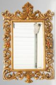 A LARGE BAROQUE STYLE GILT COMPOSITION MIRROR