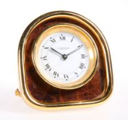 A CARTIER YELLOW-METAL STRUT CLOCK, the arch-top case housing a circular white dial, signed 'Cartier