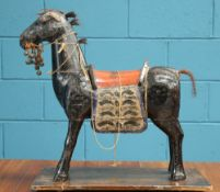 A 19TH CENTURY MIDDLE EASTEN CARVED AND PAINTED MODEL OF A HORSE