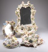 A GROUP OF FOUR CONTINENTAL FLORAL ENCRUSTED PORCELAIN FRAMED MIRRORS