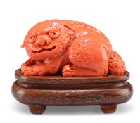 A 19TH CENTURY CHINESE CORAL CARVING OF A BUDDHISTIC LION