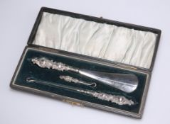 AN EDWARDIAN SILVER-HANDLED BUTTON, GLOVE AND SHOE SET