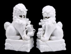 A NEAR PAIR OF CHINESE BLANC DE CHINE MODELS OF BUDDHIST LIONS