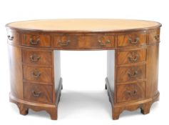A GEORGE III STYLE LEATHER INSET MAHOGANY OVAL PARTNERS DESK