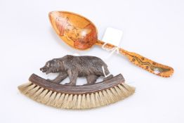 A Black Forest carved bear brush, 16cm together with a birchwood spoon decorated with a figure of