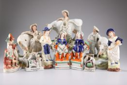 A group of Staffordshire figures comprising two milkmaids and a cow herd, largest 25cm high, a