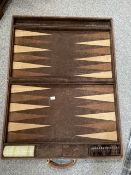 A suede leather bound backgammon set by Zarach complete with counters, 62cm by 40cm