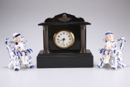Two pressed porcelain figures of boys and a black slate mantel clock