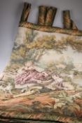 A large machine made tapestry wall hanging depicting figures in a landscape by a mill, 230cm by