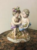 Meissen figure of two children, one holding a wreath over the others head and with a cornucopia