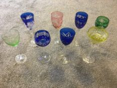 Eight mixed Bohemian coloured and hand cut crystal glasses.