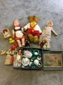 Box of vintage dolls, a bear with hump back and growler and childs ceramic tea set.