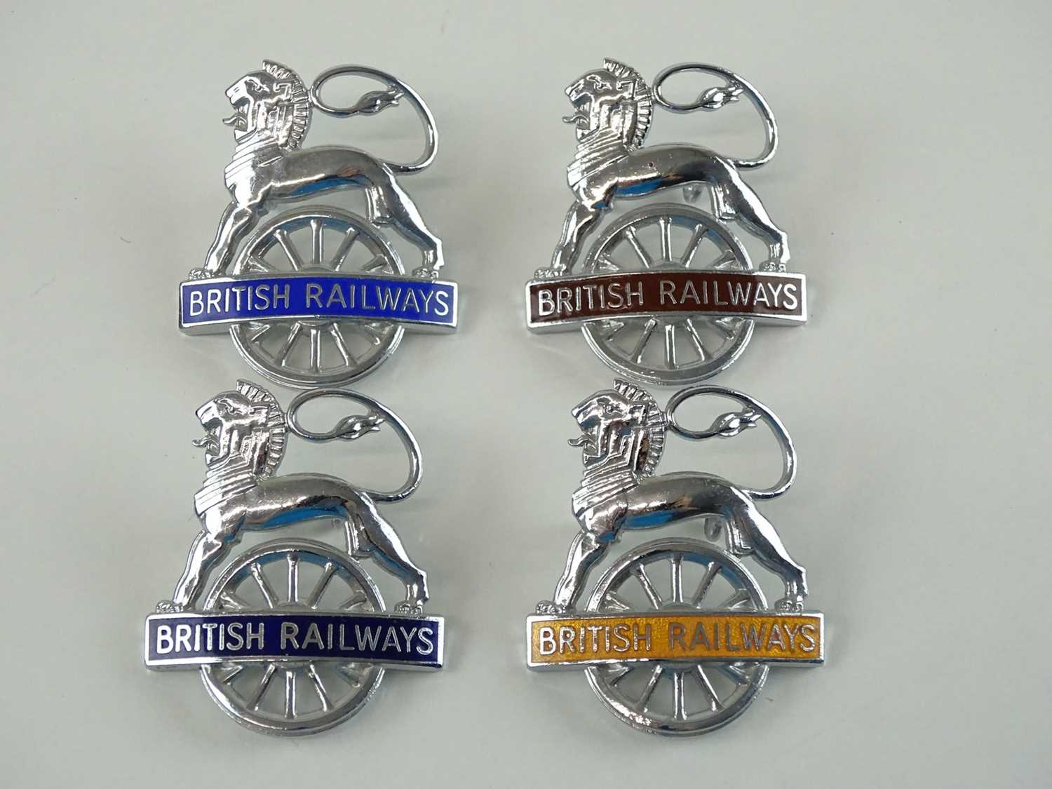 A group of British Railways lion & wheel logo cap badges - all enamelled with different region