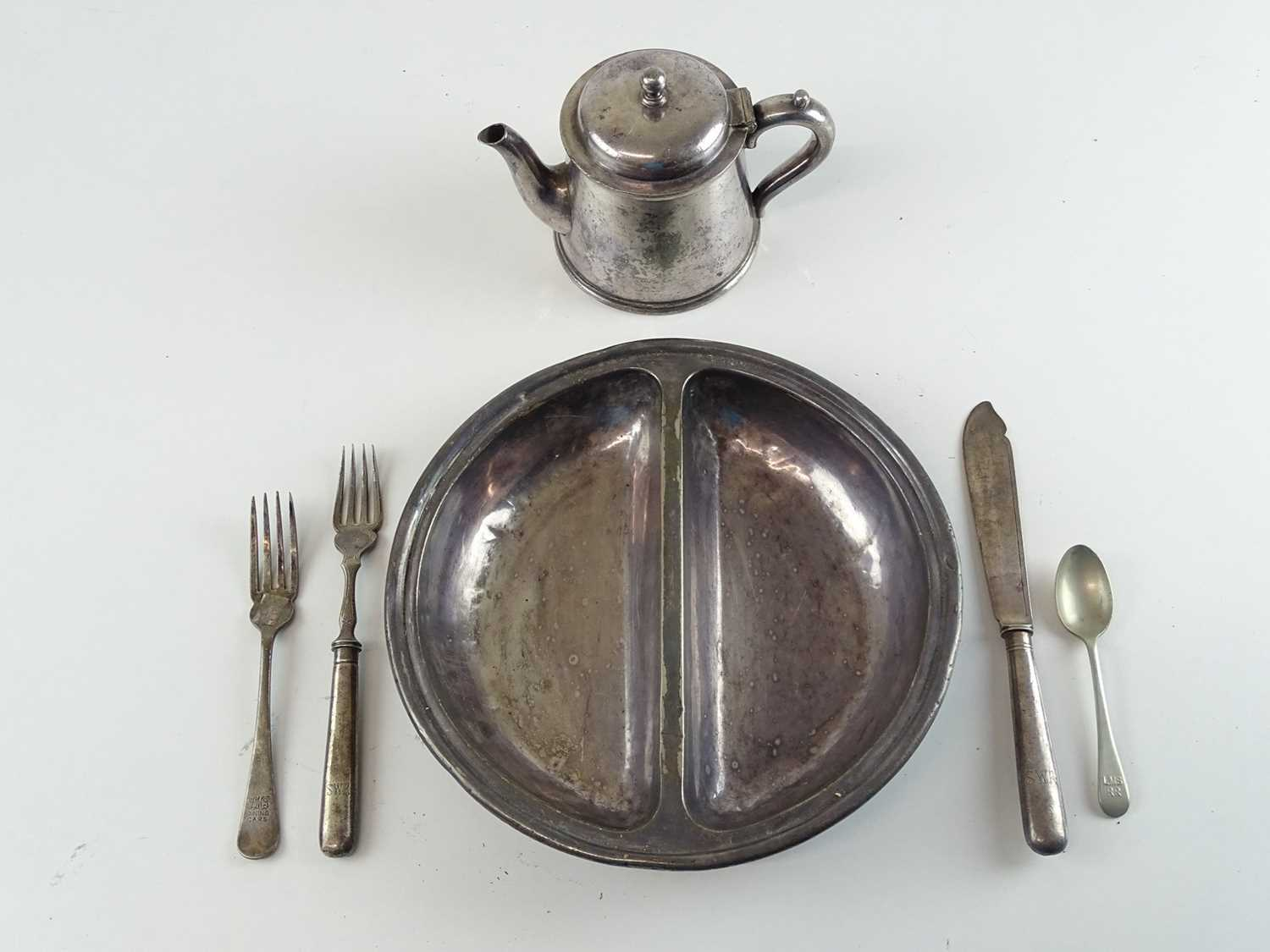 A silver plate 'place setting' comprising coffee pot, serving dish and various cutlery from