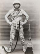 Mercury Astronaut.- Walter Schirra: Pressure suit portrait standing by a spacecraft model, 1962, …