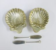 A pair of Victorian silver butter dishes of shell form complete with matching butter knives,