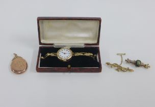 Two early 20th century 9ct gold brooches and a lady's vintage 9ct gold cased wristwatch on a 9ct