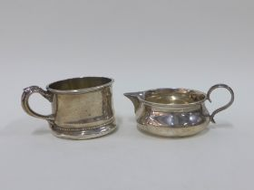 George V silver cream jug, London 1911 together with a silver cup stamped 'Sterling', 5cm high (2)