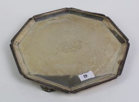 An octagonal silver presentation tray with gadrooned edge and Art Deco feet, by Walker & Hall,