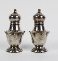 A pair of Edwardian silver pepper pots, Birmingham 1910, (2)
