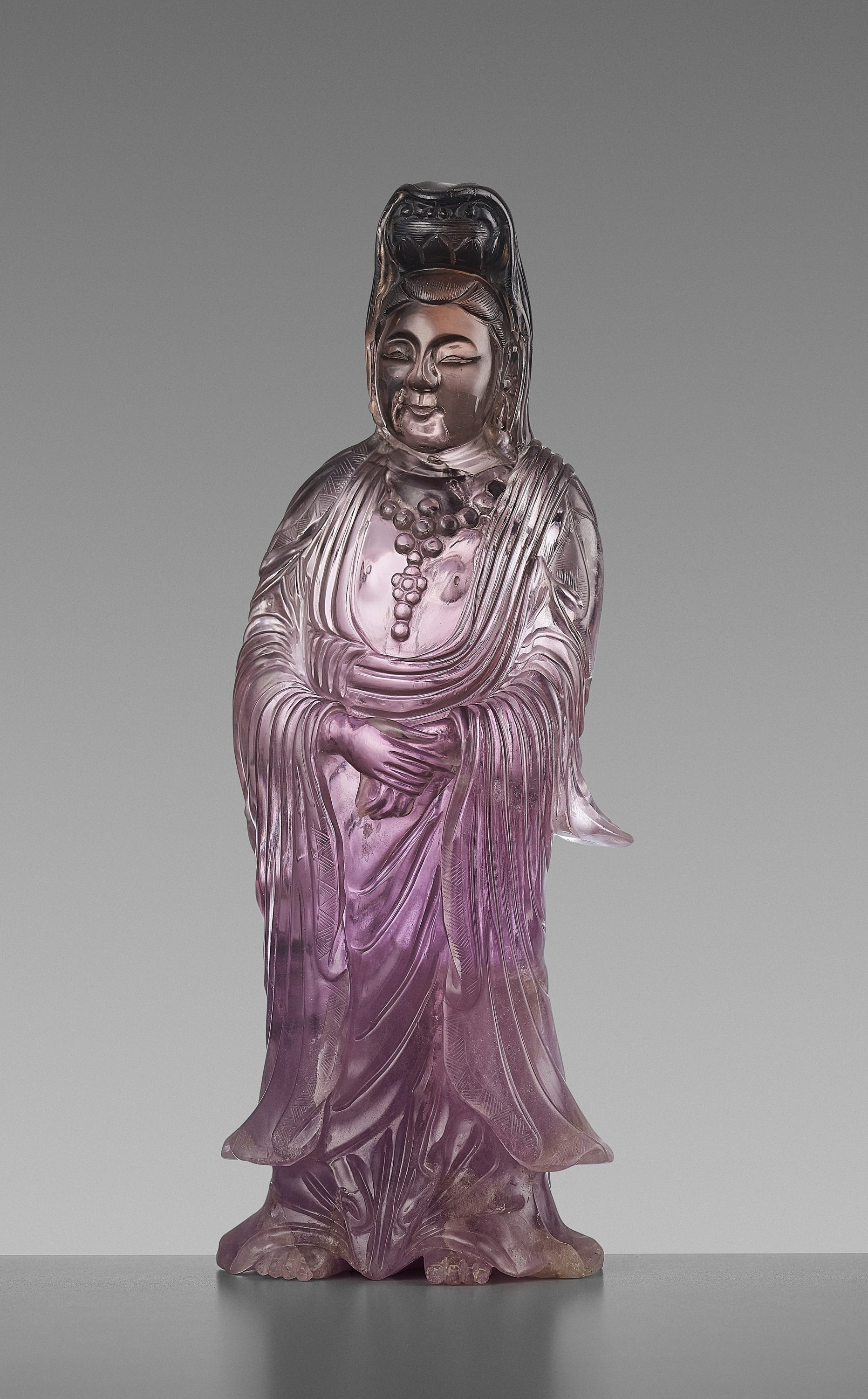 A CARVED AMETHYST FIGURE OF GUANYIN, QIANLONG MARK AND OF THE PERIOD