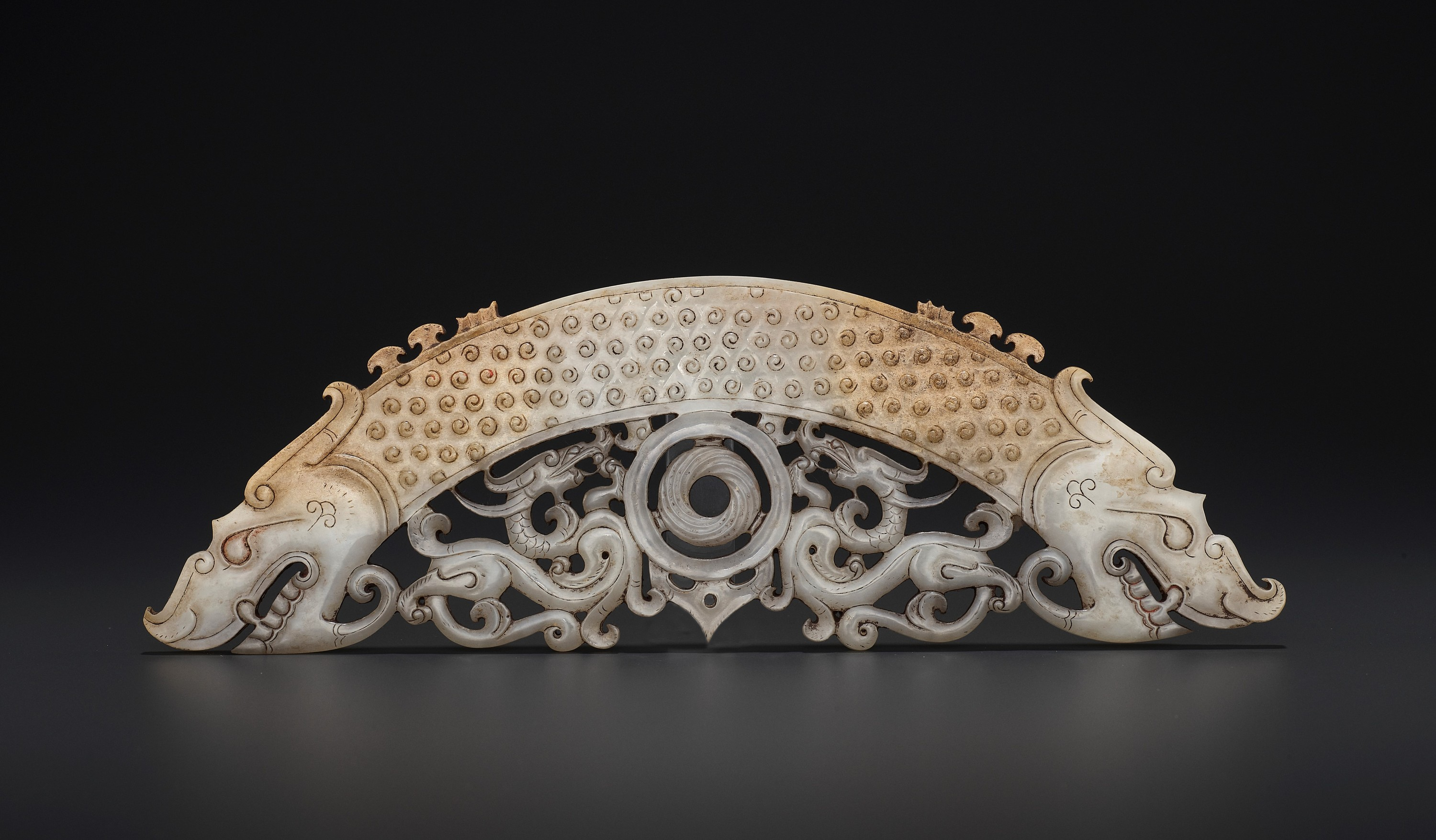 A WHITE AND RUSSET JADE 'DOUBLE DRAGON' PENDANT, HUANG, LATE EASTERN ZHOU TO HAN